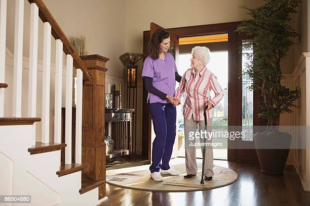 Nursing at home with woman with cane