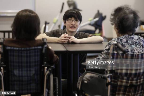 A nursing care worker center speaks to residents at the As Partners Co Asheim Nerima Garden nursing home in Tokyo Japan on Friday Aug 18 2017...