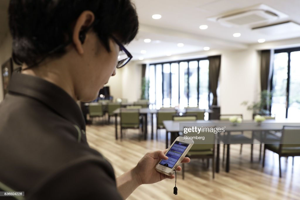 A nursing care worker looks at the residents' sleeping conditions on the 'EGAO link' system on an Apple Inc. iPhone in an arranged photograph at the As Partners Co.'s Asheim Nerima Garden nursing home in Tokyo, Japan, on Friday, Aug. 18, 2017. Caregivers can monitor the health of dozens of residents at a time from smartphones, receiving notifications if anyone so much as sits up in bed. Photographer: Kiyoshi Ota/Bloomberg via Getty Images