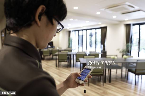A nursing care worker looks at the residents' sleeping conditions on the 'EGAO link' system on an Apple Inc iPhone in an arranged photograph at the...