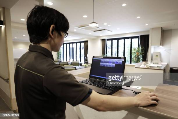 A nursing care worker looks at the residents' sleeping conditions on the 'EGAO link' system in an arranged photograph at the As Partners Co's Asheim...