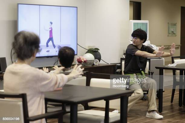 A nursing care worker right leads residents to exercise at the As Partners Co Asheim Nerima Garden nursing home in Tokyo Japan on Friday Aug 18 2017...