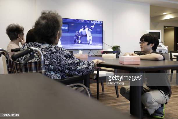 A nursing care worker right speaks to residents at the As Partners Co Asheim Nerima Garden nursing home in Tokyo Japan on Friday Aug 18 2017...