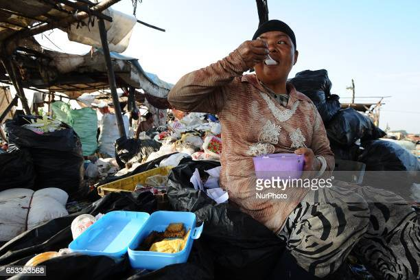 Nurtinah eats during her time work break Nurtinah a farm worker from Pucang Anom village Cerme subdistrict Bondowoso district East Java Province...