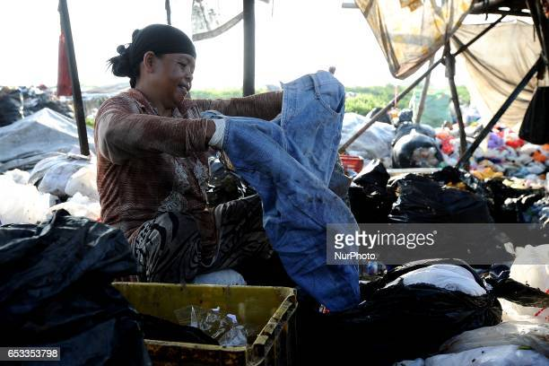 Nurtinah separates clothes from the recycled garbage Nurtinah a farm worker from Pucang Anom village Cerme subdistrict Bondowoso district East Java...