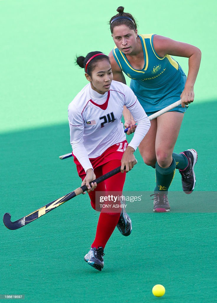 Nuru Nabihah Mansur (L) of Malaysia runs in front of Meg Pearce (R) of Australia during their women's Under 21 match at the International Super Series hockey tournament in Perth on November 22, 2012. Australia won 3-2.