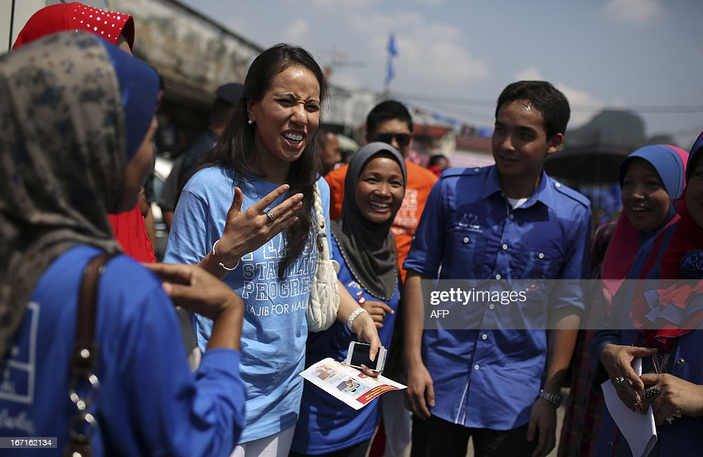 Nurul Najwa (3rd L), the daughter of Malaysia's Prime Minister Najib Razak of the ruling party National Front, and her brother Norashman (2nd R) share a light moment with party supporters as their father campaigns ahead of the 13th general election in Kuala Lumpur on April 22, 2013. Najib and opposition leader Anwar Ibrahim on April 20 kicked off their campaigns for the May 5 election, likely to be the country's closest ever.