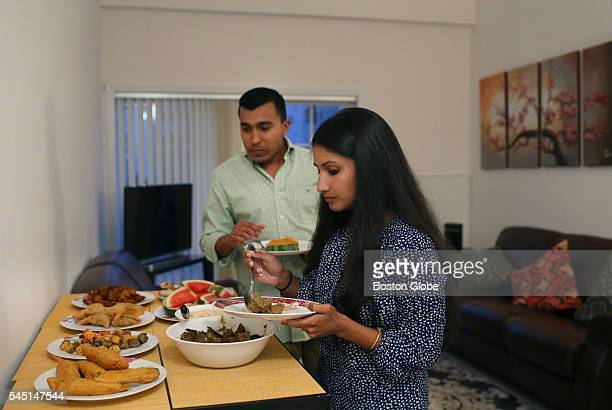 Nusrath Khan right and her husband Ahmed Amin serve themselves iftar the evening meal marking the end of a day's fast during Ramadan at their...