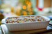 Nut roast in a baking dish with narrow depth of field and bokeh from Christmas tree lights in the background.