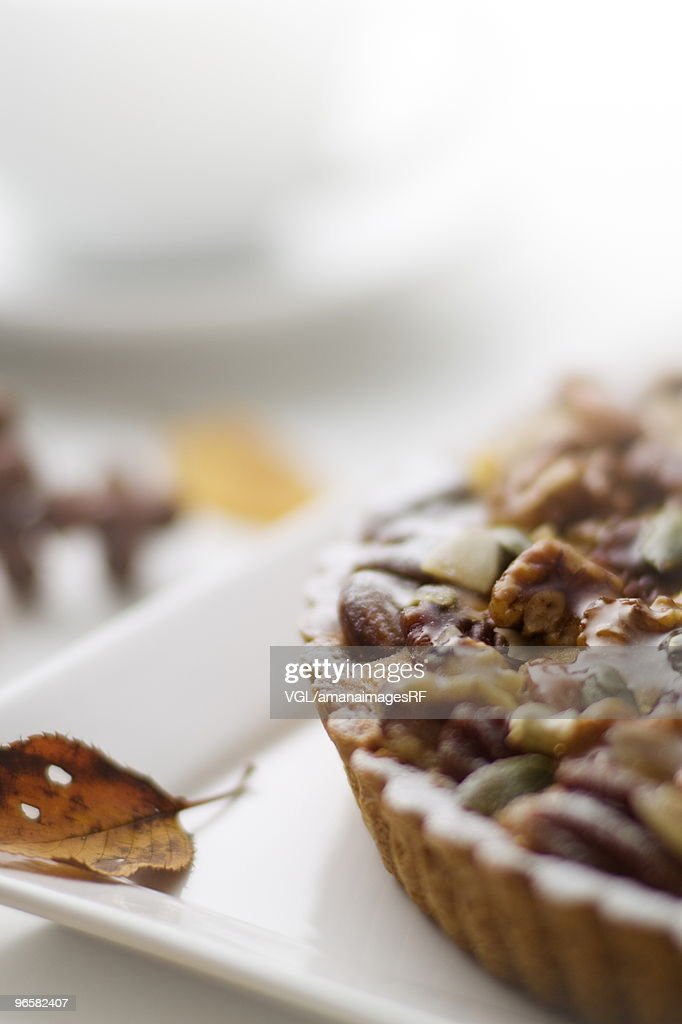 Nut tart and leaf on plate, close up : Stock Photo