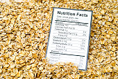 Nutrition facts of whole grain raw oats with oats background.