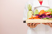 Nutritionist standing holding a tray of healthy vegetables recommended to consumers.
