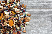 nuts and dried fruits in a bowl over rustic wooden table. top view with copy space. healthy food