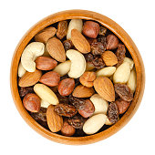 Nuts and raisins in wooden bowl. Snack mix of dried almonds, hazelnuts, cashews and raisins. Trail mix. Edible, raw, organic and vegan. Isolated macro food photo closeup from above on white background