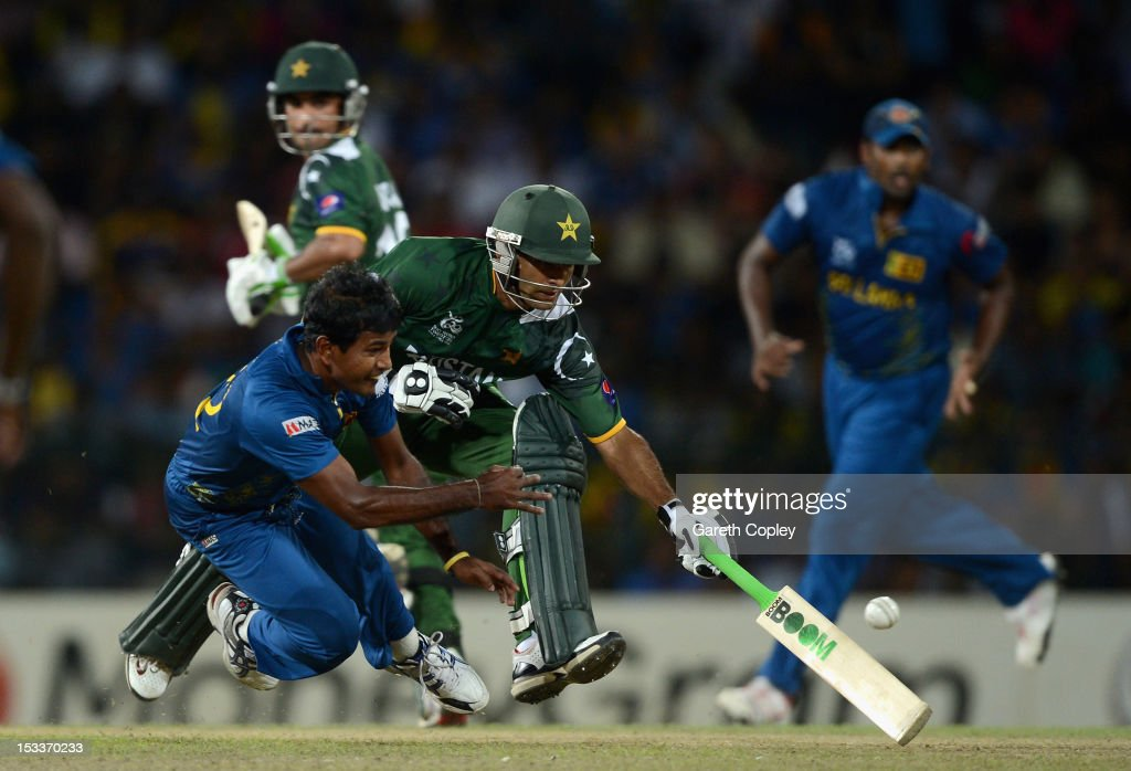 <a gi-track='captionPersonalityLinkClicked' href=/galleries/search?phrase=Nuwan+Kulasekara&family=editorial&specificpeople=608308 ng-click='$event.stopPropagation()'>Nuwan Kulasekara</a> of Sri Lanka attempts to run out <a gi-track='captionPersonalityLinkClicked' href=/galleries/search?phrase=Mohammad+Hafeez&family=editorial&specificpeople=2237440 ng-click='$event.stopPropagation()'>Mohammad Hafeez</a> of Pakistan during the ICC World Twenty20 2012 Semi Final between Sri Lanka and Pakistan at R. Premadasa Stadium on October 4, 2012 in Colombo, Sri Lanka.
