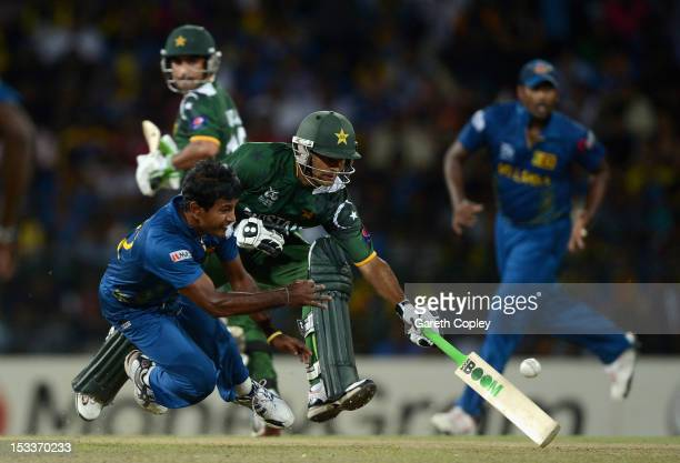 Nuwan Kulasekara of Sri Lanka attempts to run out Mohammad Hafeez of Pakistan during the ICC World Twenty20 2012 Semi Final between Sri Lanka and...