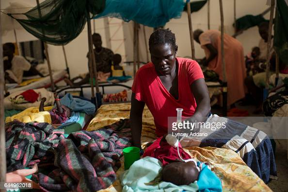 Nyakar Unwa feeds her severely malnourished daughter Monday 6 months who is being treated for malnutrition and additional complications at a tent...