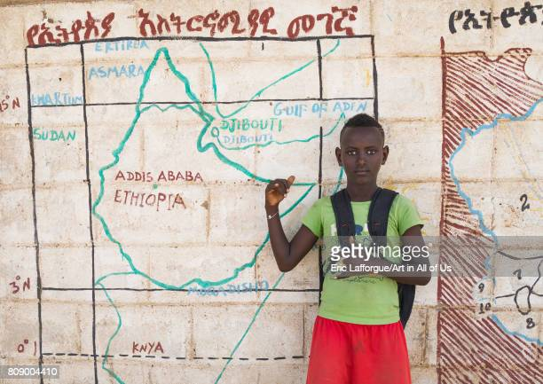 Nyangatom tribe boy in front of a school mural depicting the map of east africa Omo valley Kangate Ethiopia on June 10 2017 in Kangate Ethiopia