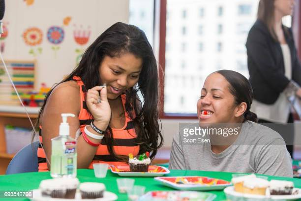 Nyasia left and mom share laughs while decorating cupcakes at a party in honor of Eversource's longstanding commitment of Boston Children's Hospital...