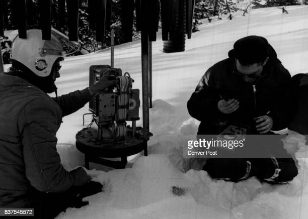 Nyborg and Coose inspect and service a delicate instrument capable of recording exactly how much precipitation falls in Medicine Bow Forest area...