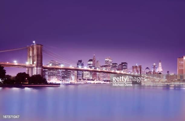 nyc skyline at night including brooklyn bridge