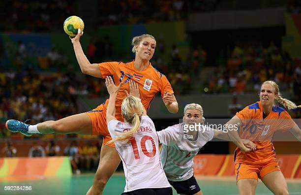 Nycke Groot of Netherlands jumps to shoot under pressure of Stine Bredal Oftedal and Veronica Kristiansen of Norway during the Women's Handball...