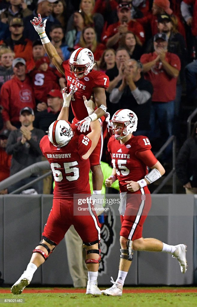 Nyheim Hines #7 of the North Carolina State Wolfpack celebrates a touchdown with teammates during their against the North Carolina Tar Heels game at Carter Finley Stadium on November 25, 2017 in Raleigh, North Carolina. North Carolina State won 33-21.