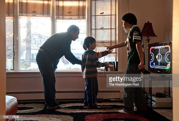 Shadid Satti playing video games on the Nintendo Wii with his sons in their home in Manhassett Hills New York on January 16 2011 from left to right...