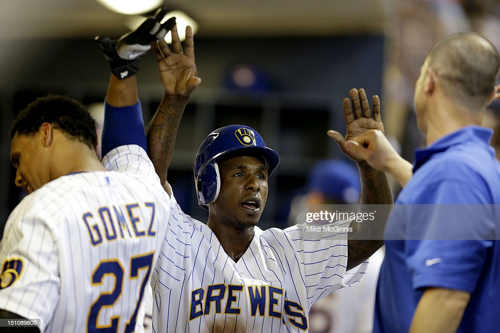 <a gi-track='captionPersonalityLinkClicked' href=/galleries/search?phrase=Nyjer+Morgan&family=editorial&specificpeople=4175372 ng-click='$event.stopPropagation()'>Nyjer Morgan</a> #2 of the Milwaukee Brewers celebrates in the dugout after scoring in the bottom of the second inning against the Pittsburgh Pirates at Miller Park on August 31, 2012 in Milwaukee, Wisconsin.