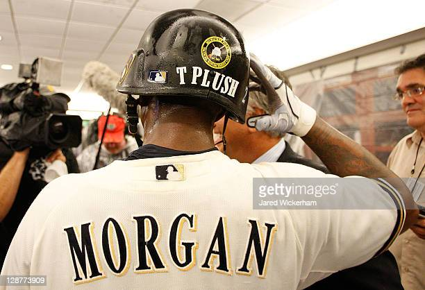 Nyjer Morgan of the Milwaukee Brewers is interviewed in the clubhouse wearing a helmet with the name 'T Plush' on the back following their win...