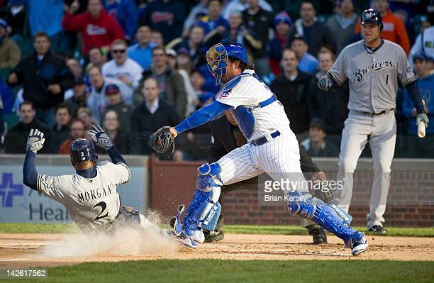 Nyjer Morgan of the Milwaukee Brewers scores on a sacrifice fly hit by teammate Aramis Ramirez as catcher Geovany Soto of the Chicago Cubs tries to...