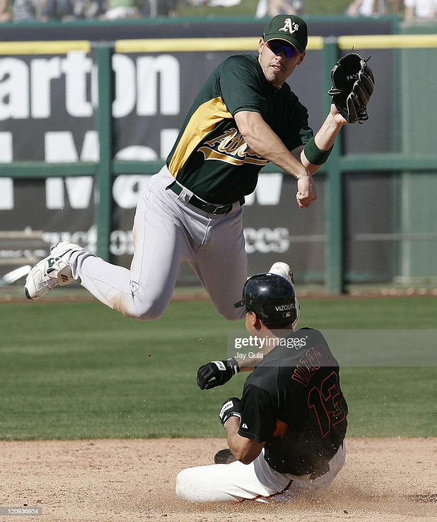 Oakland A's JJ Furmaniak throws to 1st over a sliding Omar Vizquel in Cactus League action vs the San Francisco Giants at Scottsdale Stadium in...