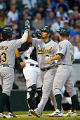 Oakland Athletics' 3rd Baseman Eric Chavez is greeted at home plate by teammates Steve Swisher and Mark Ellis after hitting a 3rd inning 3run homerun...