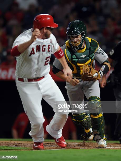 Oakland Athletics catcher Dustin Garneau chases Los Angeles Angels of Anaheim first baseman CJ Cron during a run down back towards third base in the...