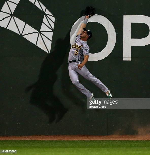Oakland Athletics center fielder Boog Powell leaps unsuccessfully for an RBI double off the Green Monster by Boston Red Sox left fielder Andrew...
