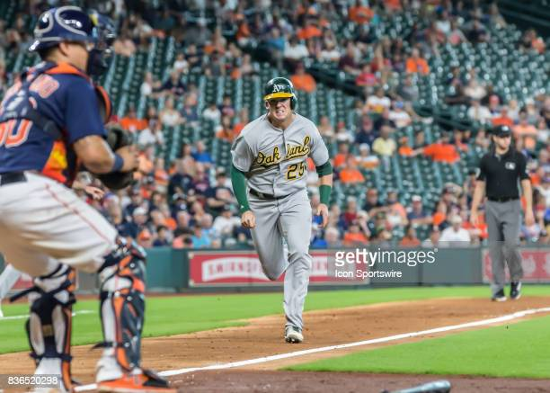 Oakland Athletics designated hitter Ryon Healy sprints to home plate to beat the tag in the sixth inning of the MLB game between the Oakland...