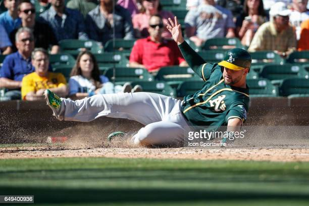 Oakland Athletics first baseman Yonder Alonso slides into home plate during the spring training baseball game between the Oakland Athletics and the...