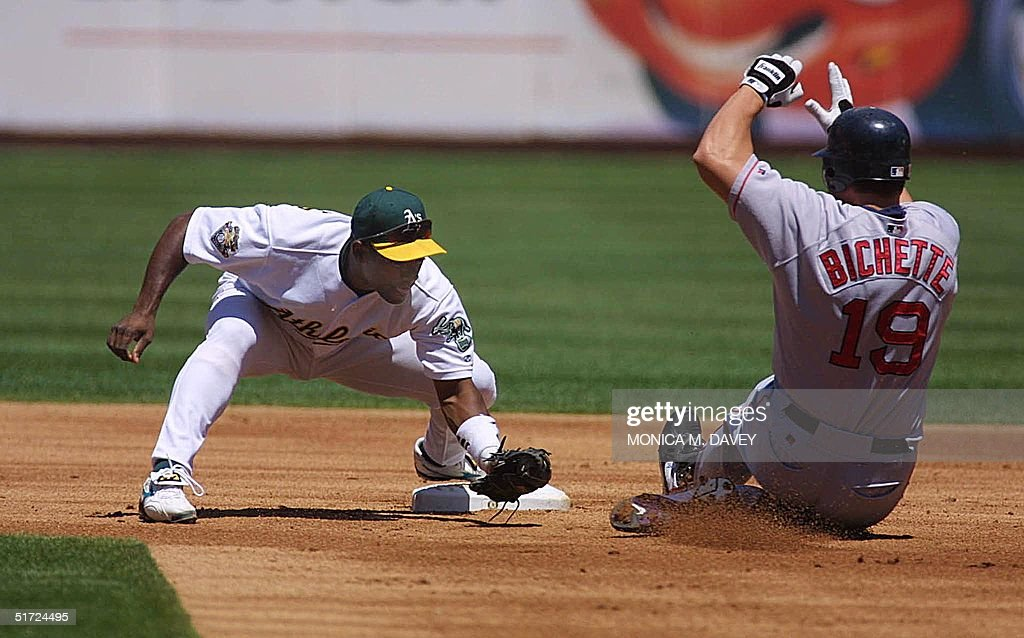 Oakland Athletics' Miguel Tejada (L) waits for Boston Red Sox's Dante Bichette at second base after Bichette tried to stretch a single into a double in the second inning 09 August 2001 in Oakland, CA. Athletics won their eighth in a row, 6-0, and go up a half game on the Red Sox in the wild card race. AFP PHOTO/Monica M. DAVEY