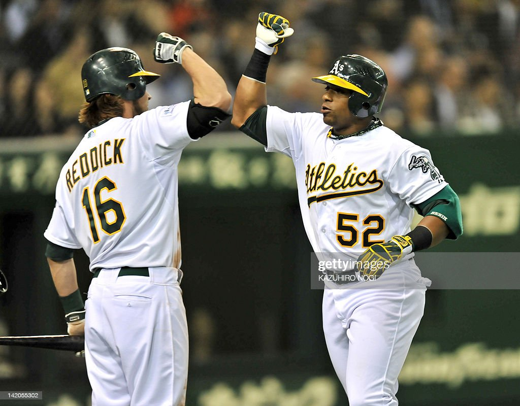 Oakland Athletics outfielder Yoenis Cespedes (R) is welcomed by teammate outfielder Josh Reddick (L) after his two-run homer in the seventh inning of the MLB 2012 Opening Series against Seattle Mariners in Tokyo on March 29, 2012. The Seattle Mariners and Oakland Athletics are here to hold the opening two-game series of the 2012 major league season, March 28-29.
