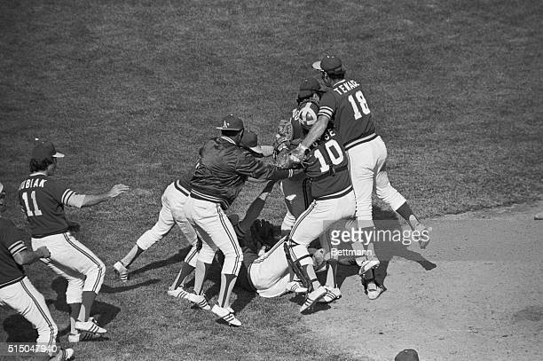 Oakland Athletics pitcher Jim 'Catfish' Hunter tumbles to ground as he is mobbed by teamates after his 30 victory over the Baltimore Orioles at...