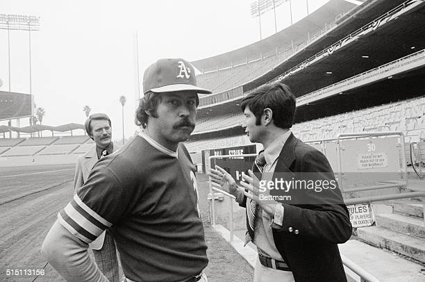 Oakland Athletics pitcher Jim 'Catfish' Hunter turns towards camera as his agent Jeery Kapstein gestures while talking to newsman Published reports...