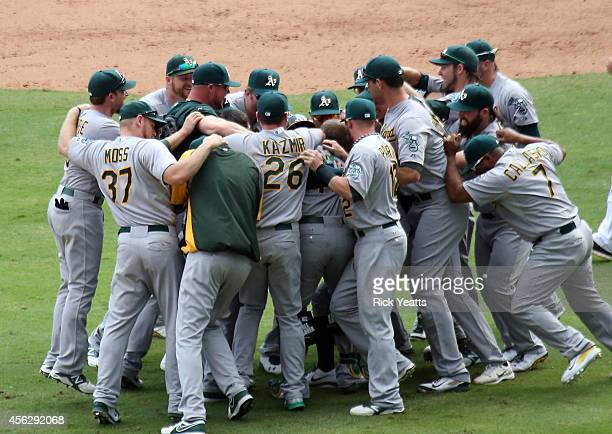 Oakland Athletics run to the field after securing a playoff spot beating the Texas Rangers 40 at Globe Life Park in Arlington on September 28 2014 in...