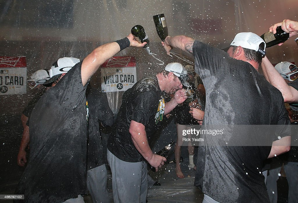 Oakland Athletics team pours Champaign on manager <a gi-track='captionPersonalityLinkClicked' href=/galleries/search?phrase=Bob+Melvin&family=editorial&specificpeople=239192 ng-click='$event.stopPropagation()'>Bob Melvin</a> #6 after securing a playoff spot beating the Texas Rangers 4-0 at Globe Life Park in Arlington on September 28, 2014 in Arlington, Texas.