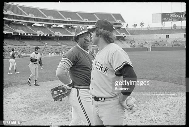 New York Yankees pitcher Jim 'Catfish' Hunter gets together with old teammate Oakland A's Reggie Jackson before the start of their game at Oakland...