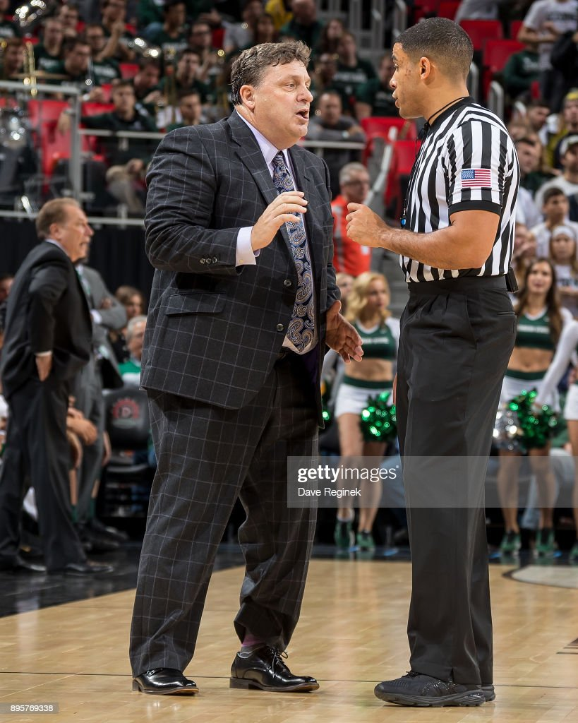 Oakland Golden Grizzlies head coach Greg Kampe talks to the referee during game two against the Michigan State Spartans of the Hitachi College Basketball Showcase at Little Caesars Arena on December 16, 2017 in Detroit, Michigan. The Spartans defeated the Grizzles 86-73.