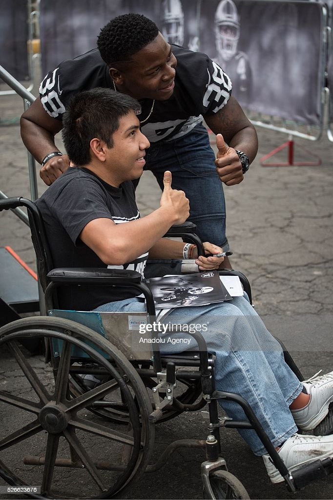 Oakland Raiders Cornerback, T. J. Carrie, poses for a picture with a fan during The Oakland Raiders Fan Fest in Mexico City, Mexico on April 30, 2016. Raiders and HoustonTexans will play at the Azteca Stadium next Nov 21, will also be the first Monday Night NFL game played outside the U.S.