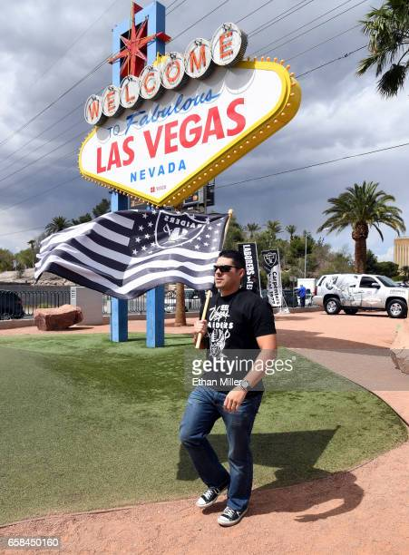 Oakland Raiders fan Matt Gutierrez of Nevada carries a Raiders flag in front of the Welcome to Fabulous Las Vegas sign after National Football League...