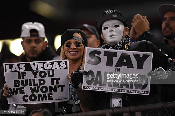 Oakland Raiders fans display signs in support of the team staying in Oakland during their game against the Denver Broncos at OaklandAlameda County...