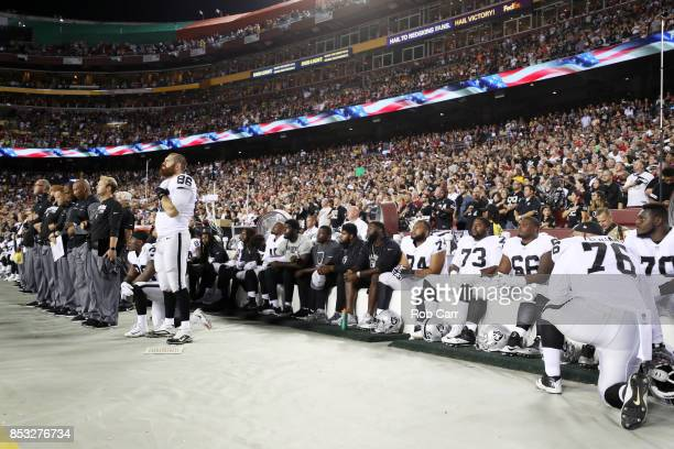 Oakland Raiders players sit during the national anthem before they take on the Washington Redskins at FedExField on September 24 2017 in Landover...