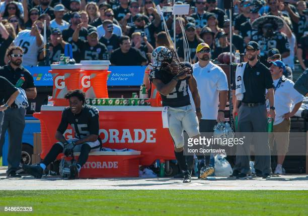 Oakland Raiders running back Marshawn Lynch enjoys himself on the sideline during the regular season game between the Oakland Raiders and the New...